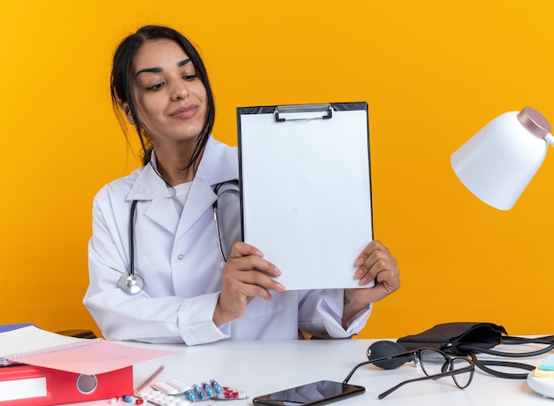 Felice giovane dottoressa che indossa una veste medica con uno stetoscopio si siede al tavolo con strumenti medici che tengono e guardano gli appunti isolati sul muro giallo