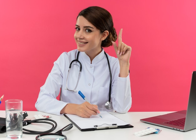 Pleased young female doctor wearing medical robe with stethoscope sitting at desk work on computer with medical tools write something on clipboard points to up on pink wall