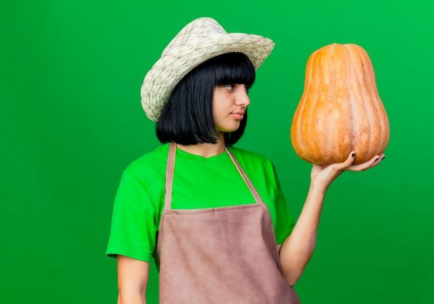 원예 모자를 쓰고 제복을 입은 기쁘게 젊은 여성 정원사가 보유하고 복사 공간이 녹색 배경에 고립 된 호박을 본다