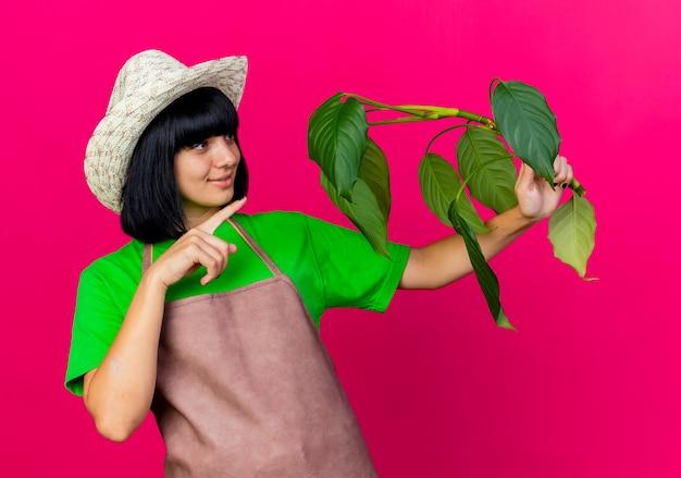 ガーデニング帽子をかぶって制服を着た若い女性の庭師が喜んでいる