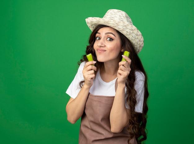Довольная молодая женщина-садовник в униформе в садовой шляпе держит сломанный острый перец, изолированный на зеленой стене с копией пространства
