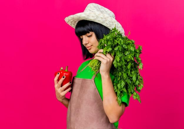 원예 모자를 쓰고 제복을 입은 기쁘게 젊은 여성 정원사는 고수풀을 보유하고 붉은 고추를 본다.