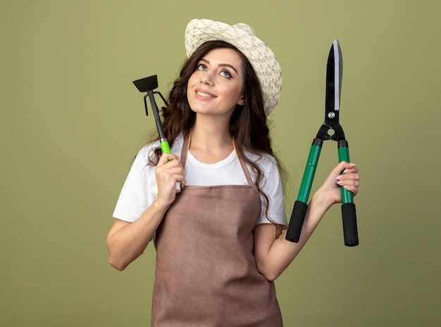 Довольная молодая женщина-садовник в униформе в садовой шляпе держит садовые ножницы и грабли, изолированные на оливково-зеленой стене
