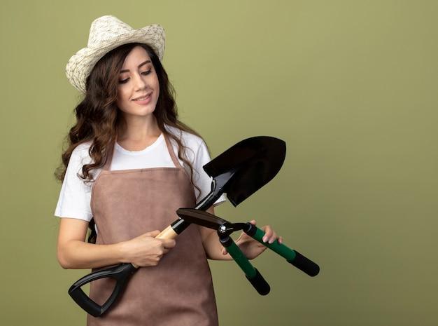 Довольная молодая женщина-садовник в униформе в садовой шляпе держит лопату и кусачки, изолированные на оливково-зеленой стене