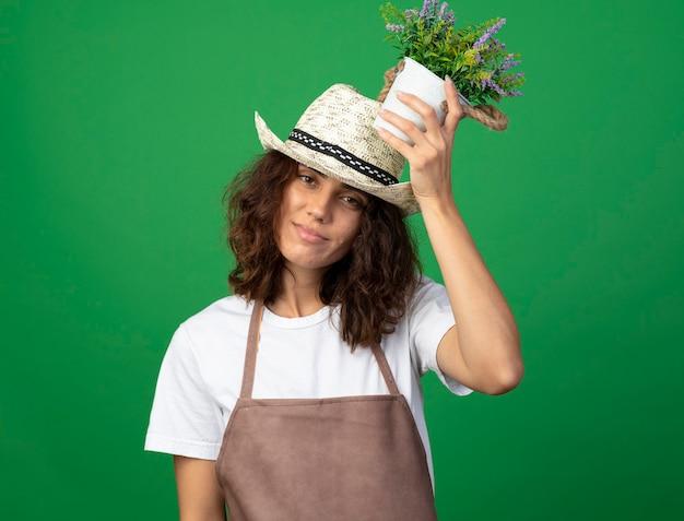 頭に植木鉢に花を置くガーデニング帽子をかぶって制服を着た若い女性の庭師を喜ばせる