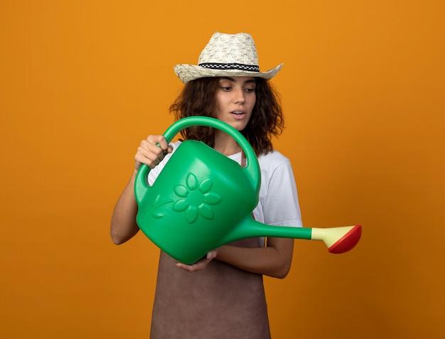 Довольная молодая женщина-садовник в униформе в садовой шляпе поливает лейкой