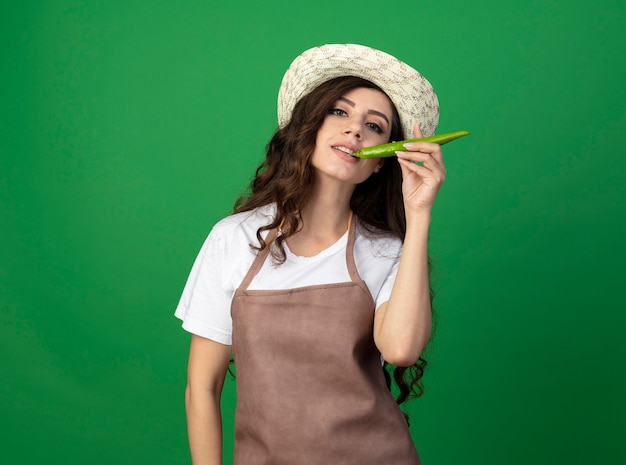 Il giovane giardiniere femminile soddisfatto in cappello da giardinaggio d'uso uniforme morde il peperoncino isolato sulla parete verde