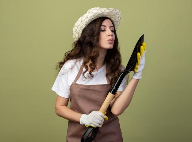 Lieta giovane giardiniere femminile in uniforme che indossa guanti e cappello da giardinaggio finge di baciare la vanga isolata sulla parete verde oliva