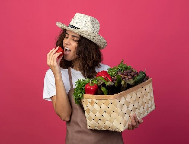 Felice giovane giardiniere femminile in uniforme che indossa cappello da giardinaggio tenendo il cesto di verdure cercando pomodoro isolato sul colore rosa