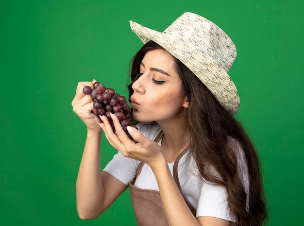 Il giovane giardiniere femminile soddisfatto in cappello da giardinaggio d'uso uniforme finge di baciare l'uva isolata sulla parete verde con lo spazio della copia