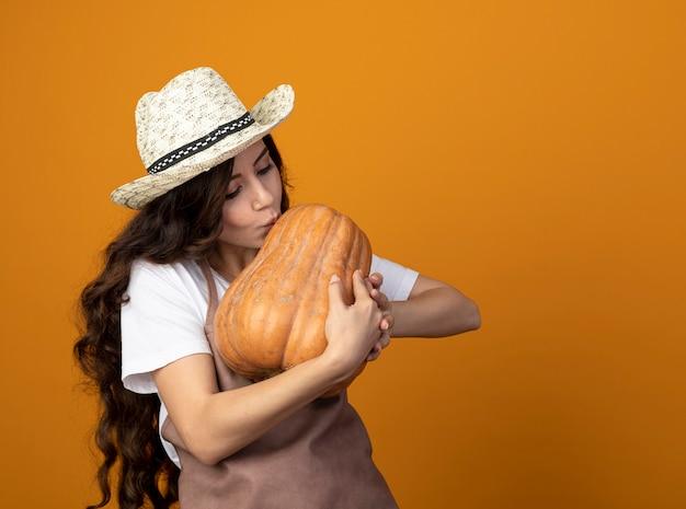Il giovane giardiniere femminile soddisfatto in cappello da giardinaggio d'uso uniforme finge di baciare la zucca isolata sulla parete arancione con lo spazio della copia