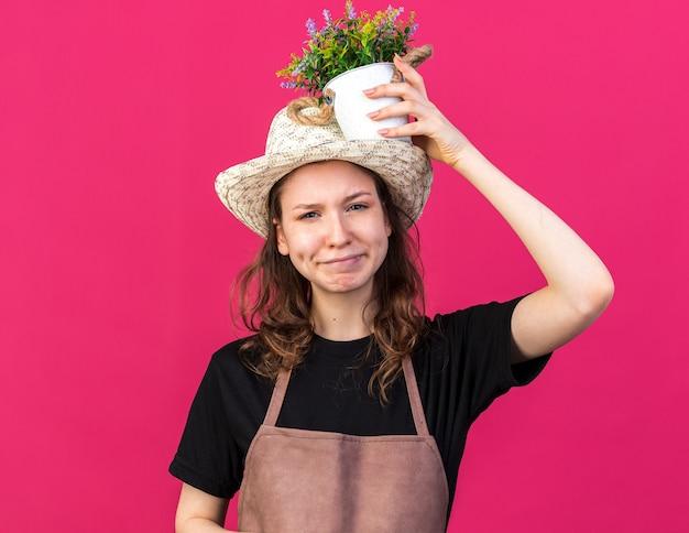 분홍색 벽에 격리된 머리에 화분에 꽃을 들고 정원용 모자를 쓴 젊은 여성 정원사를 기쁘게 생각합니다.