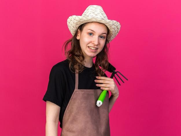 鍬熊手を保持している園芸帽子をかぶっている若い女性の庭師を喜ばせる