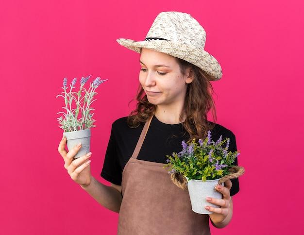 Felice giovane giardiniere femmina che indossa cappello da giardinaggio tenendo e guardando i fiori in vasi da fiori