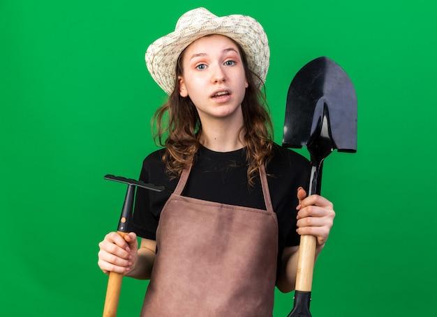 熊手とスペードを保持している園芸帽子をかぶっている若い女性の庭師を喜ばせる