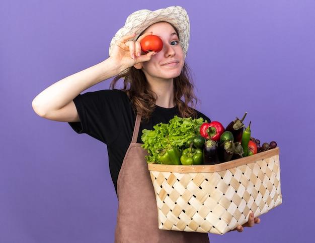 Felice giovane giardiniere femmina che indossa cappello da giardinaggio tenendo cesto di verdure che mostra gesto di sguardo con pomodoro