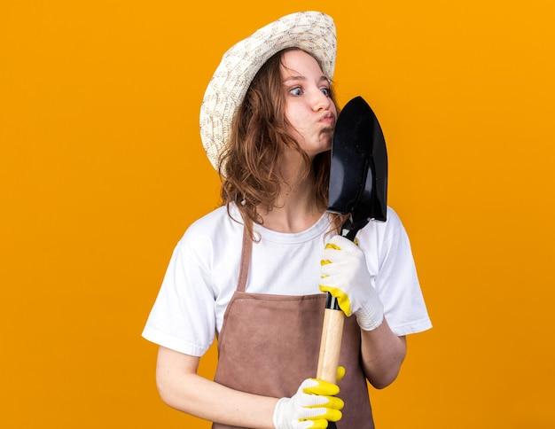 Felice giovane giardiniere femmina che indossa cappello da giardinaggio con guanti che tengono e baciano vanga