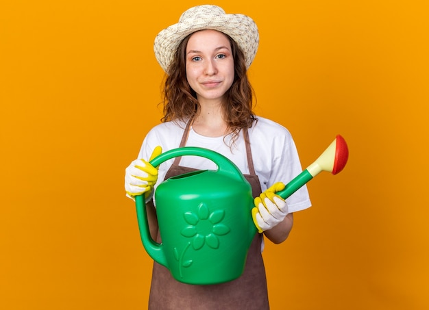 Довольная молодая женщина-садовник в садовой шляпе с перчатками держит лейку, изолированную на оранжевой стене
