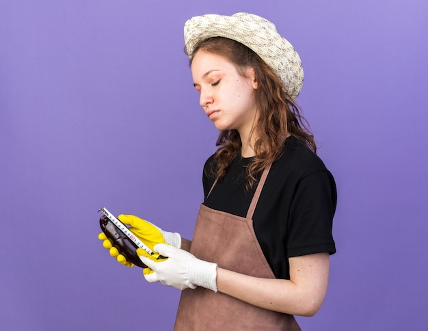 Pleased young female gardener wearing gardening hat with gloves measuring eggplant with tape measure isolated on blue wall