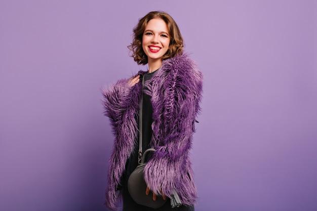 Felice giovane modello femminile con un sorriso sincero in posa su sfondo viola, tenendo la borsa grigia