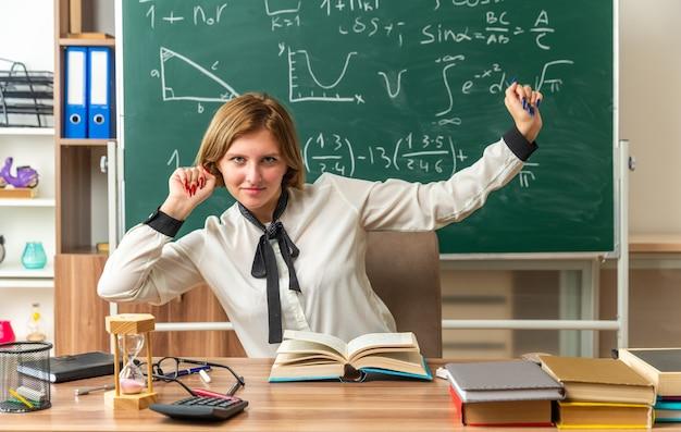 Compiaciuta giovane insegnante si siede a tavola con materiale scolastico in classe