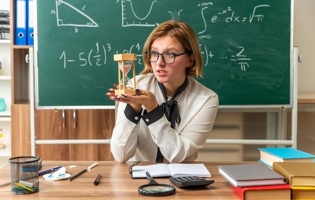 Felice giovane insegnante femminile si siede al tavolo con materiale scolastico tenendo e guardando la clessidra in classe