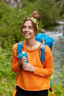 Pleased young female tourist has remarkable hiking trip, enjoys hot drink, holds flask