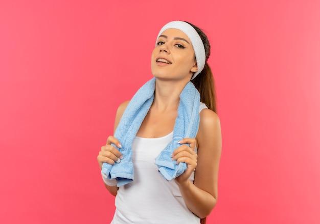 Довольная молодая фитнес-женщина в спортивной одежде с повязкой на голову и полотенцем на плече с уверенной улыбкой, стоящая над розовой стеной