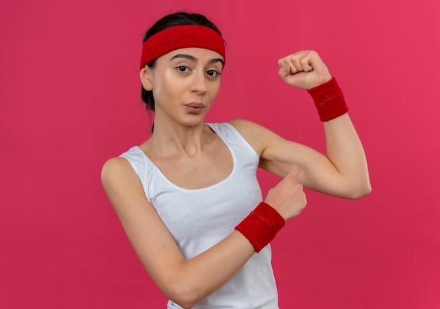 Довольная молодая фитнес-женщина в спортивной одежде с повязкой на голову, поднимающей кулак, показывающая бицепс, уверенно стоящая над розовой стеной
