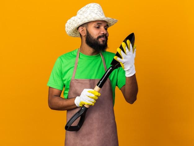 Felice giovane giardiniere afro-americano che indossa cappello e guanti da giardinaggio che tengono e guardano vanga