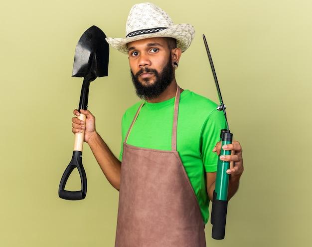 Felice giovane giardiniere afro-americano che indossa un cappello da giardinaggio con forbici e vanga isolati su una parete verde oliva