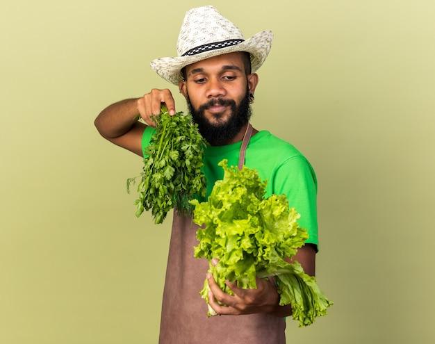 カメラでサラダを差し出してガーデニングの帽子をかぶっている若い庭師のアフリカ系アメリカ人の男を喜ばせる