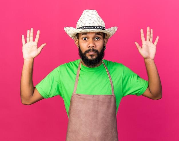 Felice giovane giardiniere afro-americano che indossa un cappello da giardinaggio alzando le mani