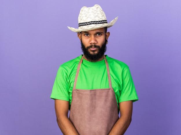 ガーデニングの帽子をかぶっている若い庭師のアフリカ系アメリカ人の男を喜ばせる