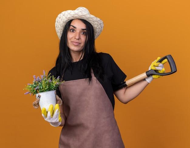 Lieta giovane ragazza giardiniere che indossa uniforme e cappello con guanti da giardiniere che tengono vanga dietro la schiena e vaso di fiori guardando davanti isolato sulla parete arancione