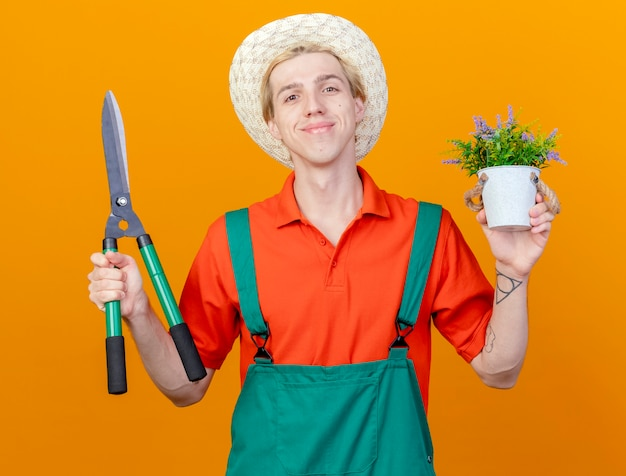 Pleased young gardener man wearing jumpsuit and hat holding hedge clippers