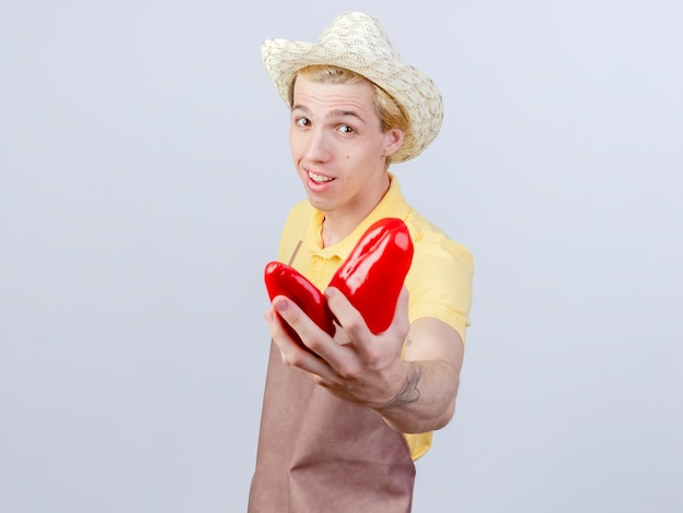 Lieto giovane giardiniere uomo che indossa tuta e cappello che mostra i peperoni rossi con un sorriso sul viso