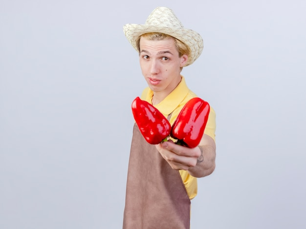 Pleased young gardener man wearing jumpsuit and hat showing red bell peppers with smile on face