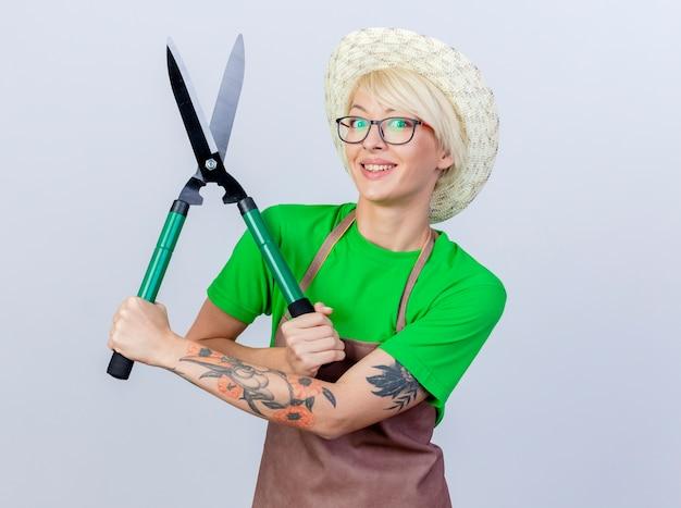 Felice giovane giardiniere donna con i capelli corti in grembiule e cappello che mostra tagliasiepi sorridendo allegramente