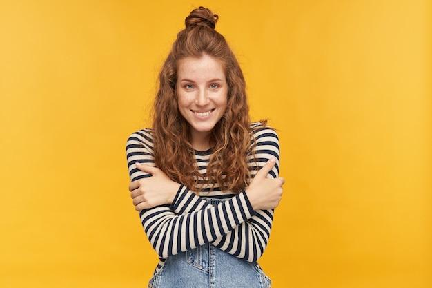La giovane femmina zenzero contenta indossa una tuta di jeans e una camicia spogliata, guarda davanti con un'espressione facciale felice, sorride ampiamente e si abbraccia isolato su muro giallo