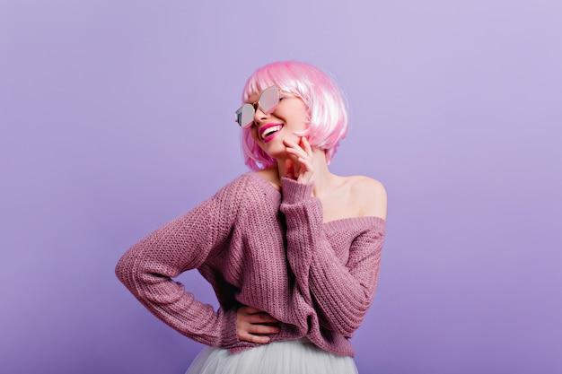 Довольная молодая девушка в парике и солнцезащитных очках с удовольствием фото замечательной женской модели с розовыми волосами, улыбающимися во время танцев на фиолетовой стене.