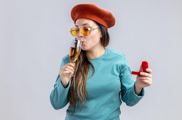 白い背景で隔離の結婚指輪とシャンパンのガラスを保持しているメガネと帽子をかぶってバレンタインデーに喜んで若い女の子