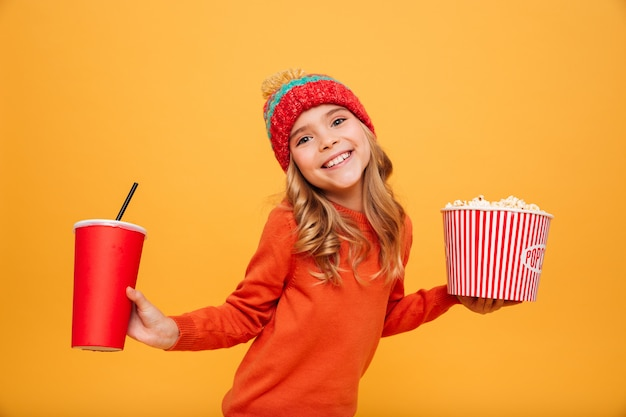 Pleased young girl in sweater and hat holding popcorn and plastic cup while looking at the camera over orange