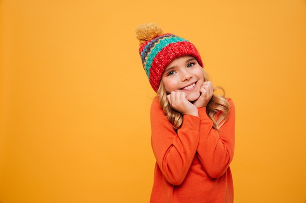 Pleased young girl in sweater and hat reclines on her arms and looking at the camera over orange