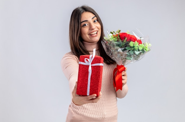 Pleased young girl on valentines day holding gift box with bouquet isolated on white background
