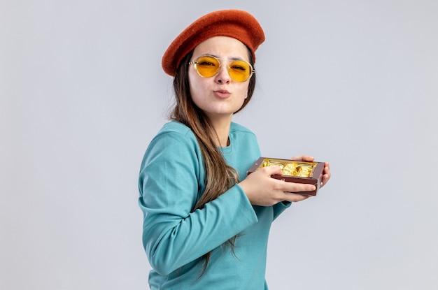 Felice ragazza il giorno di san valentino che indossa un cappello con gli occhiali che tengono una scatola di caramelle isolato su sfondo bianco