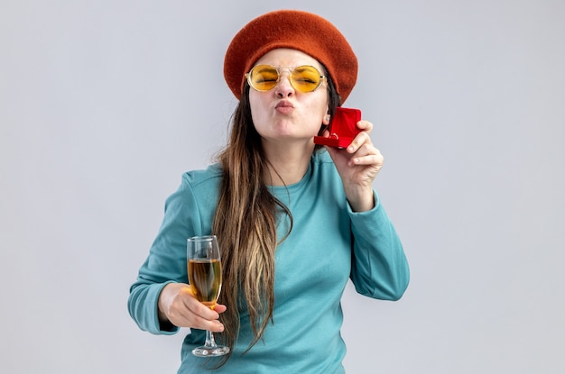 Pleased young girl on valentines day wearing hat with glasses holding glass of champagne with wedding ring showing kiss gesture isolated on white background