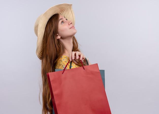 コピースペースで孤立した白いスペースを見上げて紙袋を保持している帽子をかぶって喜んで若い女の子