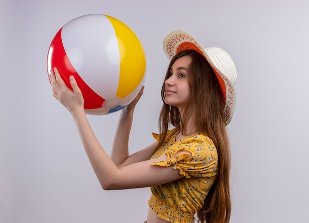 孤立した白いスペースに縦断ビューで立っているビーチボールを上げる帽子をかぶって喜んで若い女の子