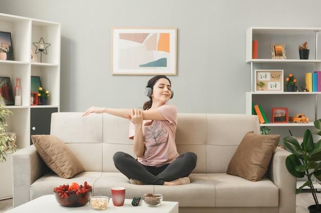 거실에 있는 커피 테이블 뒤에 소파에 앉아 요가를 하는 헤드폰을 끼고 기뻐하는 어린 소녀